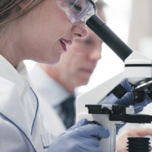 Female doctor analyzing under a microscope.